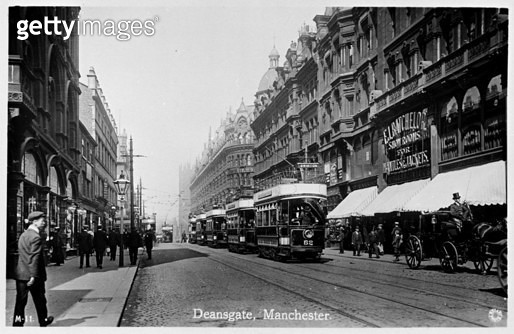 Deansgate, Manchester, with a line of trams in the middle, and the Batchelor Showrooms on the right. - gettyimageskorea