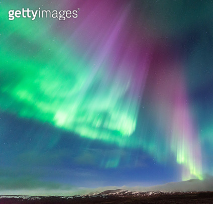 colorful northern light aurora borealis in Iceland night sky with mountain range below - gettyimageskorea