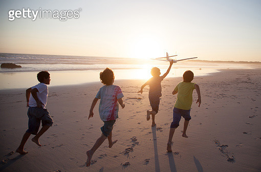Boys, aged 9-10,  running along a beach at sunset with a toy plane - gettyimageskorea