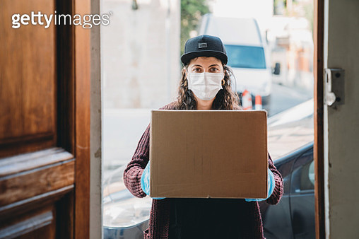 Young woman is delivering a cardboard box - View from inside the home - gettyimageskorea