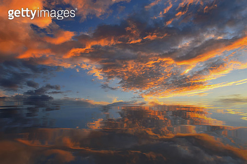 Cumulus sunset clouds with sun setting down,Clouds reflextion water on during sunset - gettyimageskorea