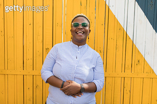 Portrait of black woman in front of a yellow wall laughing - gettyimageskorea