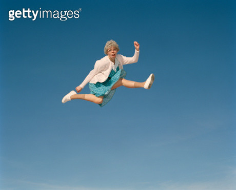 Senior woman leaping in mid air, portrait - gettyimageskorea
