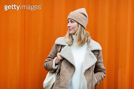 Beautiful Young Caucasian Woman 30 Years Old In Casual Clothing Near Orange Container Wall. Student - gettyimageskorea