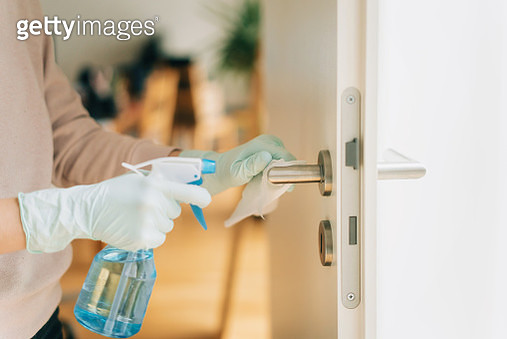 Woman cleaning a door handle with a disinfection spray and disposable wipe - gettyimageskorea