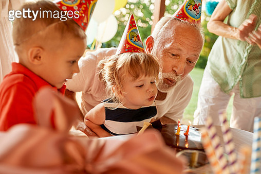 Grandfather and grandchildren blowing out candles on birthday cake on a garden party - gettyimageskorea