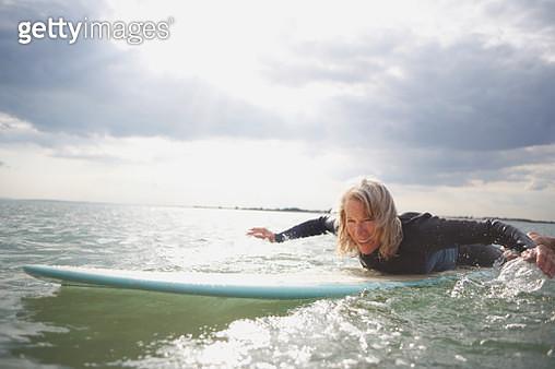 Senior woman on surfboard in sea, paddleboarding - gettyimageskorea