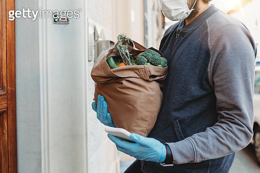 A volunteer is delivering a bag of vegetables and fruit - gettyimageskorea