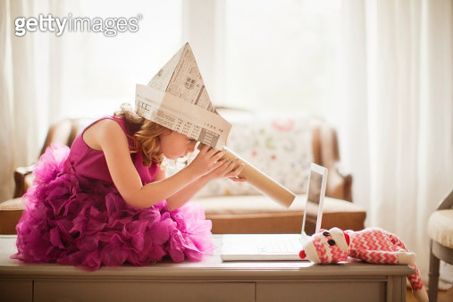 Young girl in a pink dress wearing a newspaper hat is using a kitchen roll as a telescope. Girl is looking at a computer screen while sitting on a table. Monkey stuffed animal is visible in the foreground. - gettyimageskorea