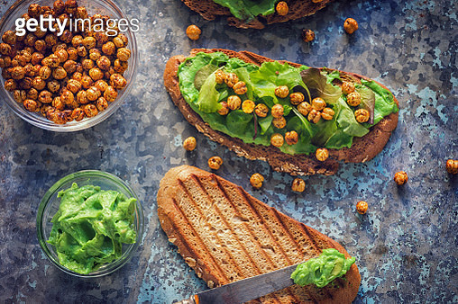 Avocado toast topped with hummus, salad and crispy roasted chickpeas - gettyimageskorea
