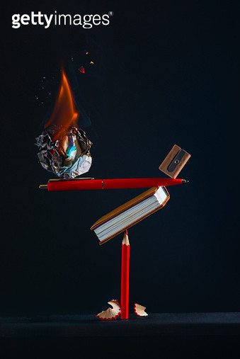 Imagination and writing concept, burning paper ball balancing on a pen and a pencil - gettyimageskorea