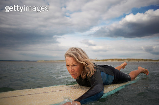 Senior woman on surfboard in sea, paddleboarding - gettyimageskorea