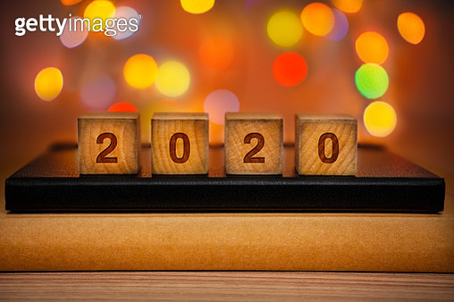2020 Text on Wood Block Against Abstract Colorful Illuminated Defocused Bokeh Lights Background. - gettyimageskorea