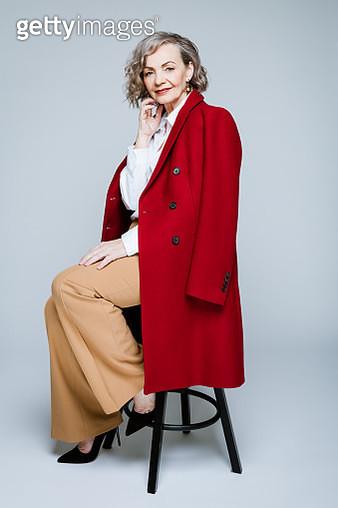 Elegance elderly lady wearing red coat and white shirt sitting on stool against grey background, smiling at camera. Studio shot of female designer. - gettyimageskorea