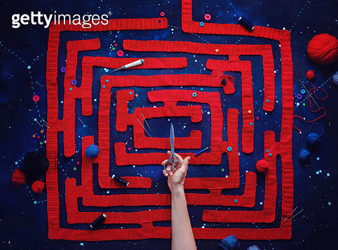 Knitted maze with a hand holding scissors, DIY concept, creative flat lay - gettyimageskorea