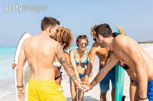 Group of friends on the beach stacking hands - gettyimageskorea