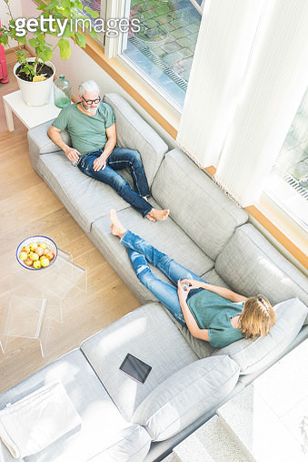 Mature couple relaxing on couch at home - gettyimageskorea