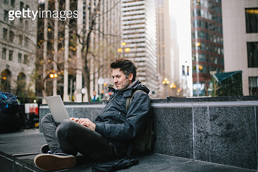 Young IT professional sitting outdoors, finishing work on the laptop, in San Francisco, California. - gettyimageskorea