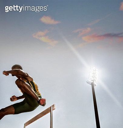 Track and field athlete clearing hurdle - gettyimageskorea