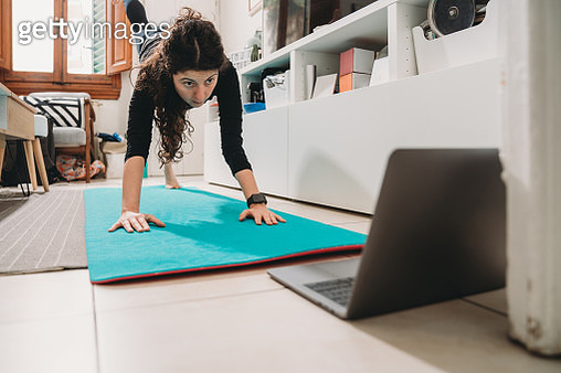 Young woman practicing yoga at home with a laptop during Coronavirus Covid-19 quarantine. - gettyimageskorea