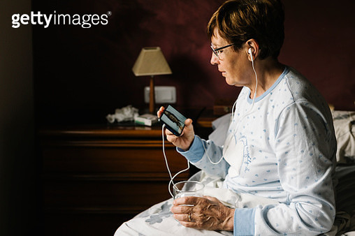 Ill woman discussing with doctor over video call through smart phone in bedroom at home - gettyimageskorea