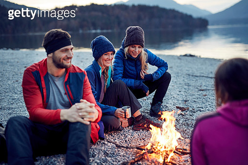 Smiling friends sitting around campfire at lakeshore - gettyimageskorea
