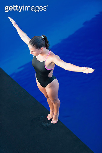High Angle View Of Mid Adult Woman Standing On Diving Board Over Swimming Pool - gettyimageskorea