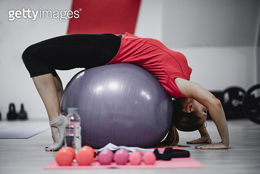 Young Female Doing Balance Pilates Exercise on Fitness Ball in Gym - gettyimageskorea
