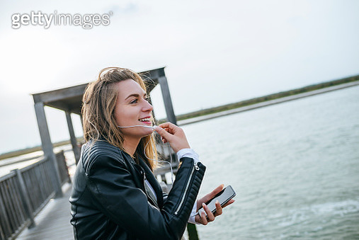 Young woman on the phone standing on boardwalk - gettyimageskorea