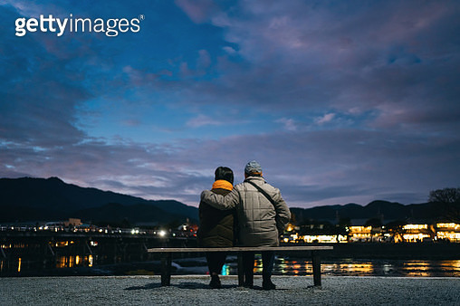 Rear view of senior couple sitting side by side on a bench enjoying the sunset by the lake while visiting traditional Japanese town in Higashiyama, Kyoto, Japan at twilight - gettyimageskorea