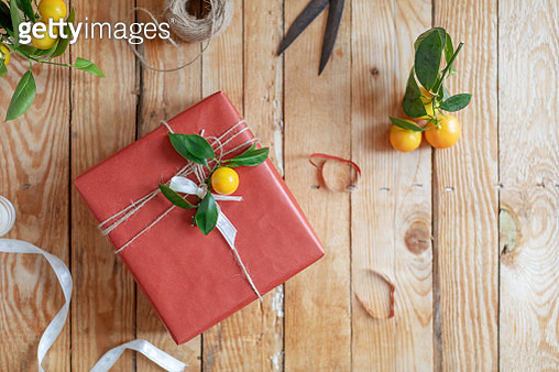Present wrapped in red paper decorated with branch of mandarine tree - gettyimageskorea