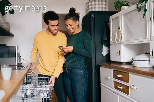 Woman smiling while showing smart phone to boyfriend while standing in kitchen - gettyimageskorea