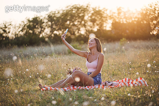 Woman using her mobile phone during a solo picnic in nature - gettyimageskorea