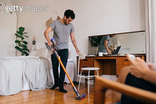 Full length of man cleaning bedroom with vacuum cleaner - gettyimageskorea