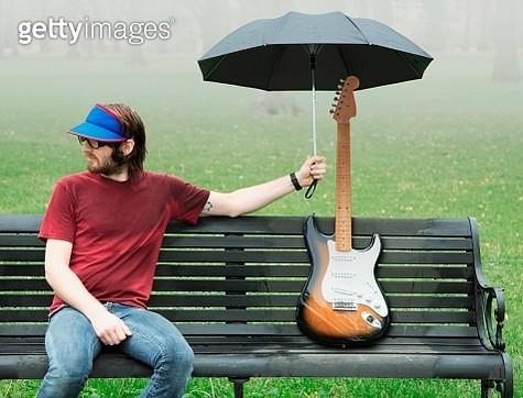 Man holding umbrella over electric guitar - gettyimageskorea