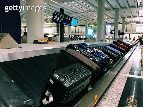 Row Of Suitcases On Conveyor Belt At Airport - gettyimageskorea