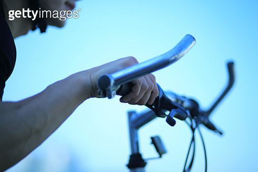 Man holding handle bars on bicycle, close-up - gettyimageskorea
