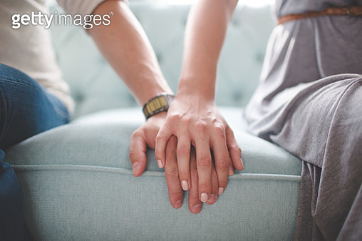 Waist photo of man and woman holding hands while sitting on a couch - gettyimageskorea
