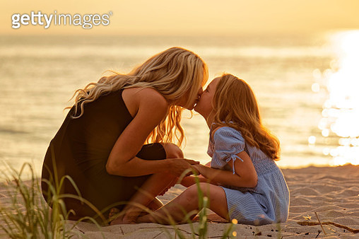 A young Mother and Daughter hold hands and share a kiss at sunset at the beach while sitting in the sand.   The two are silhouetted by a brilliant orange sunset over Georgian Bay in Tiny Township near Wasaga Beach, Ontario , Canada as they share a relaxin - gettyimageskorea