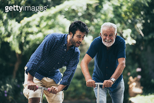 Playful Father And Son On Push Scooter - gettyimageskorea