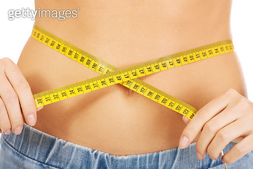 Midsection Of Woman Measuring Waist Against White Background - gettyimageskorea