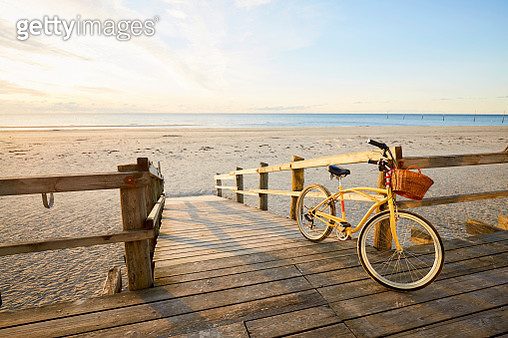 Yellow beachcruiser bicycle leaning at a railing at an empty beach during sunrise - gettyimageskorea