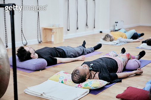 People lying down on an exercise studio floor relaxing after a sound therapy session - gettyimageskorea