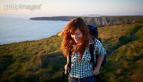 Woman hiking along coastal path - gettyimageskorea