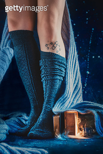 Tiny door under a wool blanket and woman legs in warm stockings, cozy reading winter concept - gettyimageskorea