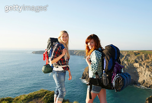 Two female hiking friends stand atop an Atlantic cliff - gettyimageskorea