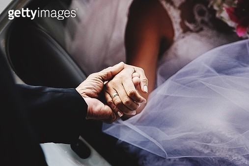 Man Holding Hands Of Bride While Sitting In Car - gettyimageskorea