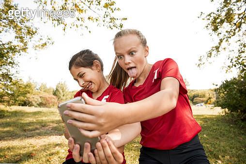 Cheerful girls taking selfie in park - gettyimageskorea