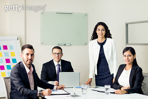Four executives having business meeting and smiling at camera - gettyimageskorea
