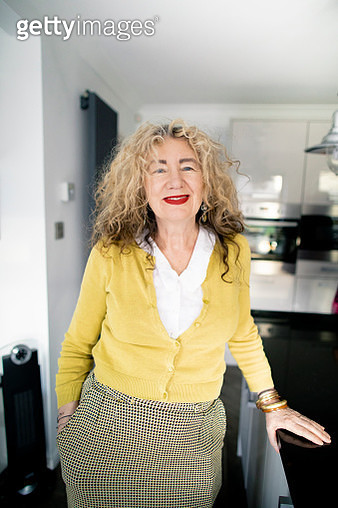 Happy and energetic woman stands in the kitchen smiling at the camera. She looks modern and hipster - gettyimageskorea